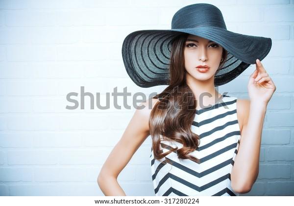 Porträt einer schönen anmutigen Frau in elegantem Hut mit einem breiten Brimm. Schönheit, Modekonzept.