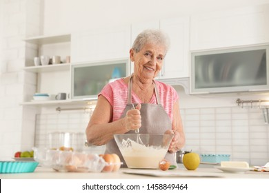 Portrait of beautiful grandmother cooking in kitchen