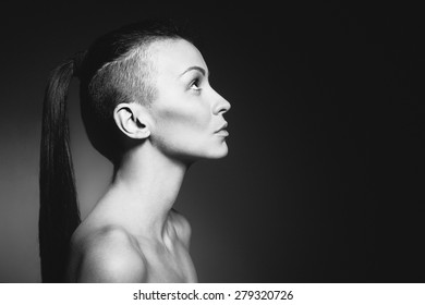 Portrait of a beautiful hairstyle woman on dark background. Developed from RAW; retouched with special care and attention./Beautiful hairstyle woman