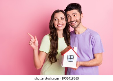 Portrait of beautiful handsome trendy cheerful friends friendship holding home showing copy space credit loan isolated on pink color background