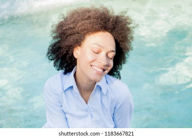 Portrait of Beautiful Happy Afro American Young Woman, smiling mixed race female relaxing near water fountain, closed eyes , sunny light reflects on the face