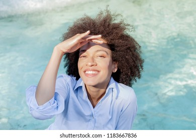 Portrait of Beautiful Happy Afro American Young Woman, smiling black woman relaxing near water fountain,looking at the camera , sunny light reflects on the face