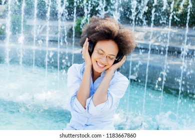 Portrait of Beautiful Happy Afro American Young Woman Listening Music with wireless headphones, closed eyes, outdoor
