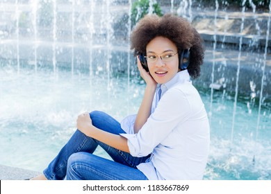 Portrait of Beautiful Happy Afro American Young Woman Listening Music with wireless headphones, looking at the side, outdoor