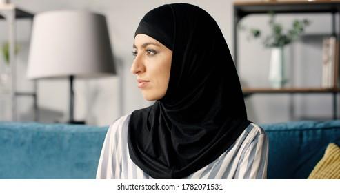 Portrait of beautiful happy Arabic Emirati lady in hijab at home.