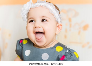 Portrait of beautiful happy baby girl with white flower on head