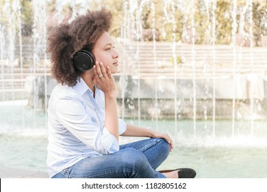 Portrait of Beautiful Happy Black Young Woman With Afro Hair Style Listening Music