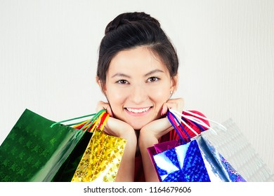 portrait of beautiful happy brunette female shopaholic holding shopping bags . concept of shopaholism and total sale sales