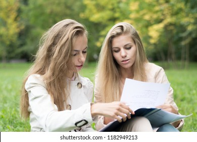 Portrait of a beautiful happy cheerful cute young ladies girls students sitting with copybooks in park outdoors on green grass