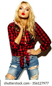 portrait of beautiful happy cute smiling blonde woman bad girl in casual red hipster winter checkered flannel shirt and blue jeans clothes with red lips gives air kiss