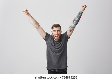 Portrait of beautiful happy encouraged caucasian man with beard and tattooed arm rising hands, screaming in full volume, cheering for favourite football team on stadium with friends.