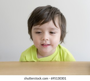 Portrait of beautiful with happy face of little boy smiling looking at down wooden table, concept for healthy kid