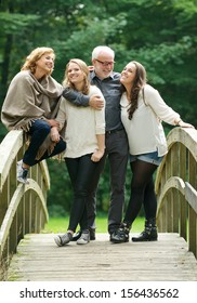 Portrait of a beautiful happy family standing together in a bridge in the woods