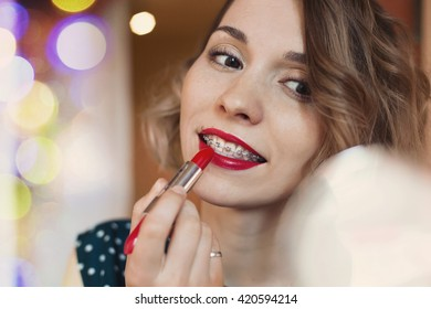 Portrait of Beautiful happy female with brace coloring her lips with red lipstick