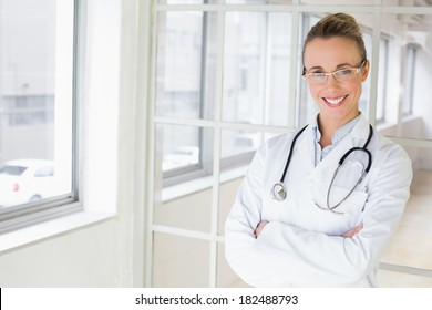 Portrait of a beautiful happy female doctor standing with arms crossed in the hospital
