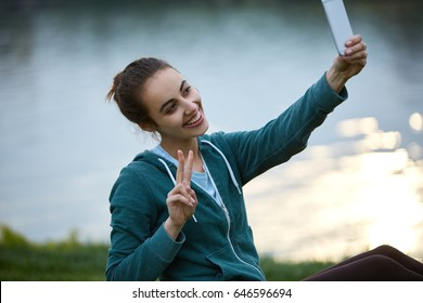 Portrait of beautiful happy girl in sportswear with small urban backpack on the shore of a lake or sea. woman makes selfie photo or video call.