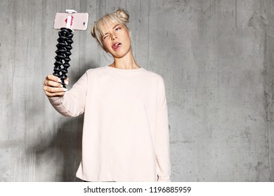 Portrait of beautiful happy girl taking selfie standing on grey background. Stylish blogger dressed in pink sweater. Copy space in right side. Fun and technology concept