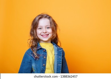Portrait of beautiful happy little curly girl on orange background