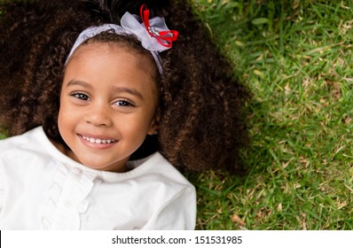 Portrait of a beautiful happy little girl lying outdoors