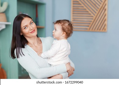 Portrait of a beautiful happy mom and little baby looking at camera.