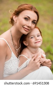 portrait of beautiful happy mother and daughter hugging and smiling at camera in park