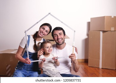 Portrait of a beautiful happy and smiling family just arrived in the new house to start a new journey together. Concept of: love, family, home.