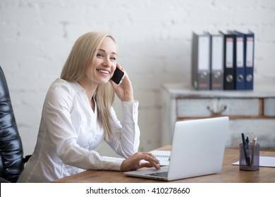 Portrait of beautiful happy smiling young office woman working on laptop at office desk. Attractive cheerful model in smart casual clothing using smartphone and computer, making call. Indoors
