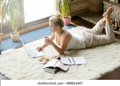 Portrait of beautiful happy smiling young woman lying on white carpet with laptop, books and cup of tea in modern cozy living room interior, listening music, studying and relaxing at home