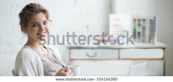 Porträt einer schönen, glücklich lächelnden jungen Designerin, die am Schreibtisch des Hauses mit einer Tasse Kaffee und Computer sitzt. Horizontaler Fotobanner für das Design von Website-Header mit Kopienraum für Text