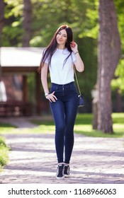 Portrait of beautiful happy stylish woman in blue jeans and white t-shirt, walking on the street. Fashion woman lifestyle. Woman style, trendy outfit. Beauty nature scene with colorful background