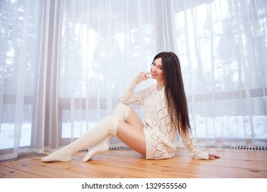 Portrait of beautiful happy stylish woman sitting on the floor near the window at the house. Winter forest at the window. Fashion woman lifestyle. Woman style, trendy outfit. Winter vacation.