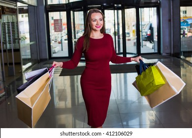 Portrait of beautiful happy  welld-dressed  woman with shopping bags. Shopping center. Successful shopping day.
