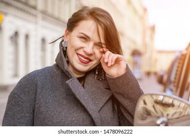 portrait of beautiful happy woman in coat outside smiling.