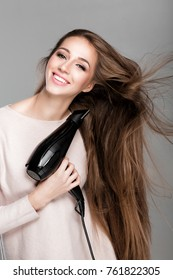 portrait of beautiful happy woman drying her long hair with dryer over gray background