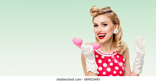 Portrait of beautiful happy woman with phone, dressed in pin-up style, on green background. Caucasian blond model posing in retro studio shoot. Copyspace area for advertising slogan or text message.