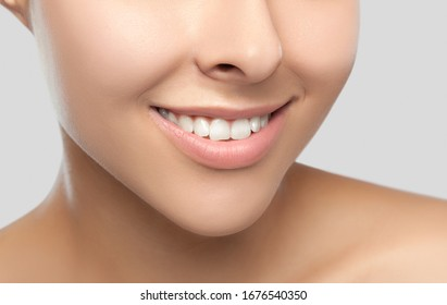 Portrait of a beautiful happy woman with a beautiful smile, clean and healthy skin and nude makeup on a gray background. Cosmetology skin care and makeup. Smile close up.