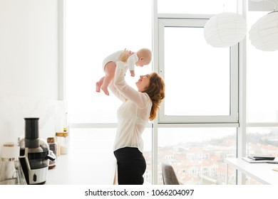 Portrait of beautiful happy woman standing and holding her pretty little baby in hands with big windows on background