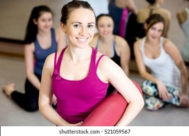 Portrait of beautiful happy yogi girl wearing bright tank top is holding folded pink yoga mat after training lesson in fitness center or gym, her class partners sitting on the background