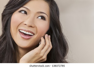 Portrait of a beautiful happy young Chinese Asian Oriental woman talking on her cell phone