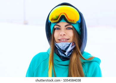 Portrait of beautiful happy young snowboarder girl in snowboard goggles.