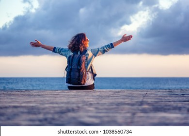 portrait of a beautiful happy young woman sitting on a wooden pier on the background of the sea and a beautiful sunset and admiring the scenery. Embrace the world, hands up