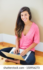 Portrait of beautiful happy young woman sitting on floor with a laptop smiling - Indoor