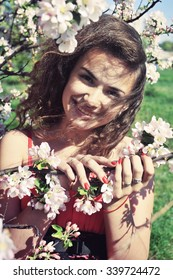 Portrait of beautiful happy young woman at the blooming tree in the park. Pretty smiling girl in a flowering spring garden