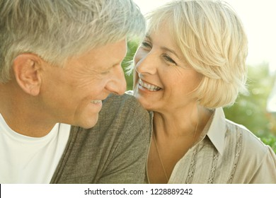 Portrait of beautiful healthy senior couple joyfully smiling with golden light, heads together with happy expression, outdoors. Mature people enjoying active lifestyle, closeness.