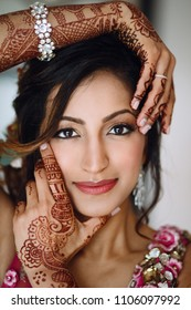 Portrait of beautiful Hindu bride holding hands with henna tattoos before her face