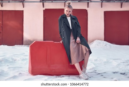 Portrait of a beautiful hipster blonde woman wearing fashion long coat and dress on the winter street