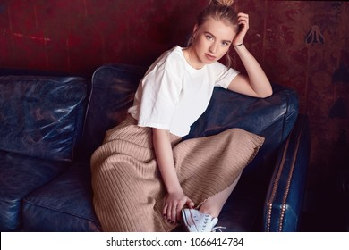 Portrait of a beautiful hipster blonde woman wearing white t-shirt and dress sitting on blue couch