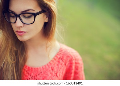 portrait of a beautiful hipster girl in glasses close up