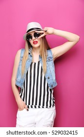 Portrait of a beautiful hipster girl on pink background