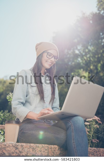 Portrait of beautiful hipster woman  chatting on laptop in the park